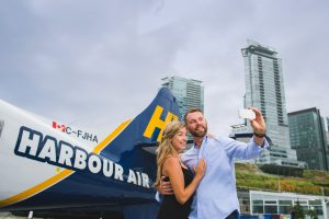 Couple taking a selfie in front of Harbour Air seaplane